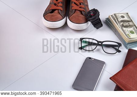 Arrangement Of Mens Accessories. Smartphone With Glasses, Shoes And Money. Isolated On White Backgro