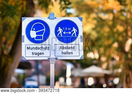 Signs for face mask and distance requirement in German city center with text saying \'wear face mask\' and \'keep distance\'