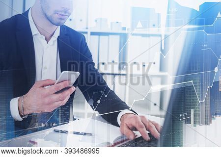 Hands Of Businessman Using Smartphone And Laptop In Blurry Office With Double Exposure Of Financial