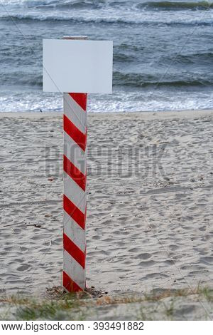 A Post With An Empty Sign. Sandy Beach. Information Index. Painted Post With Red And White Stripes.