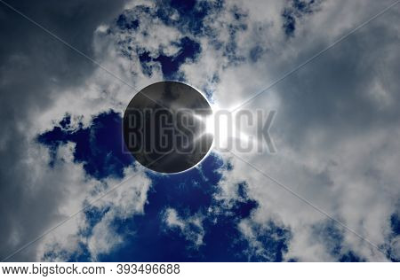 Solar Eclipse And Clouds. Solar Eclipse, Natural Phenomenon When Moon Passes Between Planet Earth An