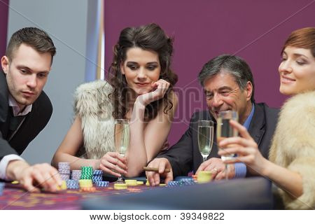 People sitting at the table looking while man placing a bet
