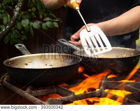 Picnic In Nature. Frying Pan On Fire On M. A Man Is Stirring Food On A Frying Pan