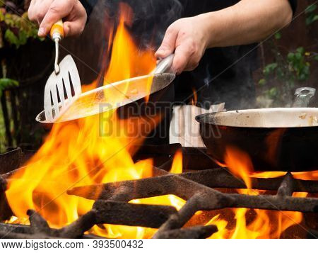 Cooking On The Grill In A Frying Pan. Frying Pan On Fire. A Man Stirs Food In A Frying Pan