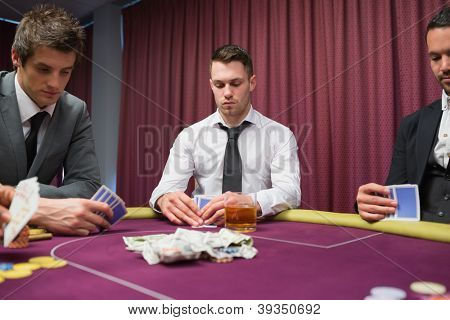 Men looking at their hands in high stakes poker game in casino
