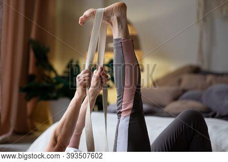 Senior Woman Working Out, Warming Up Using Yogic Belt, Lying In Yoga Supta Padangushthasana