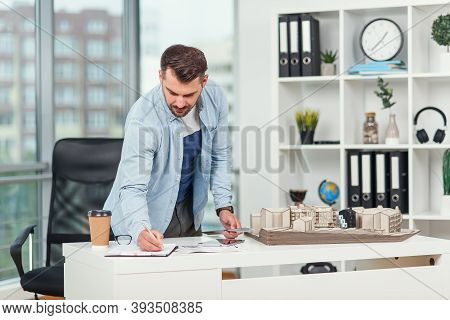 Handsome Bearded Engineer Works On Construction Project, Examines The Model On Which He Works And No