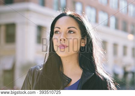 Latina Female Stands With Strength While Looking Off To The Left - Goal Achievement - Big City - Day