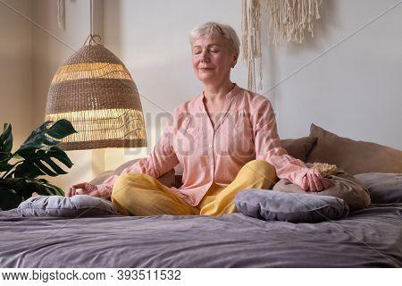 Senior Caucasian Woman Meditating Practicing Yoga Indoors.