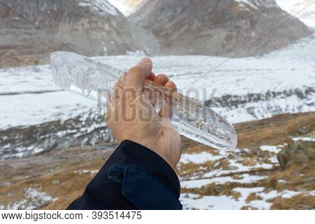 Close Up Of Icicle Held In Front Of Glacier And Mountain Landscape At The Aletsch Glacier. Showing M