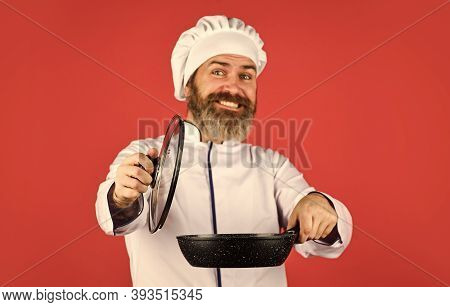 Cooking With Passion. Bearded Man Hold Cooking Pan. Preparing Food In Kitchen. Husband In Chef Hat O