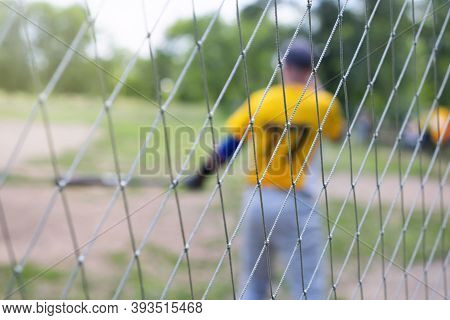 Baseball Player In Blur On The Field, Over A Wire Mesh Fence