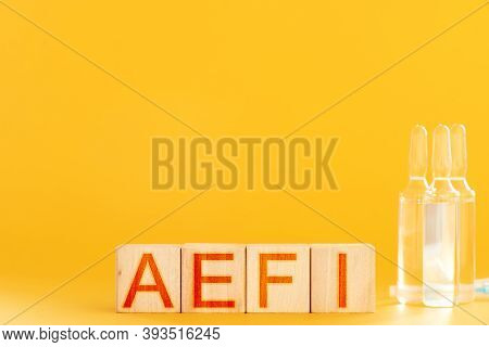 Aefi. Wooden Cubes With The Inscription Aefi On An Orange Background. Concept Of Complications After