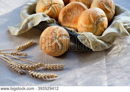 Kaiser Or Vienna Rolls On Baking Paper. Table Covered With Beige Linen Tablecloth.