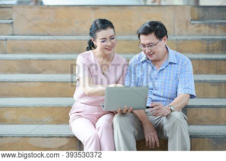 Senior Asian Traveler Couple Husband And Wife In Pink And Blue Shirt With White Nice Hat Sitting On