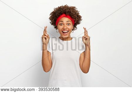 Photo Of Delighted Dark Skinned Young Woman With Afro Hairstyle, Crosses Fingers For Good Luck, Wait