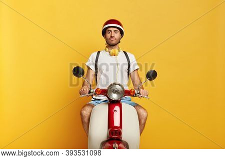Impressed Handsome Young Man Looks With Scared Face Expression, Has Trip On Motorbike, Works As Cour