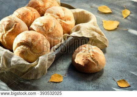 Kaiser, Or Vienna Buns In Bread Basket On Dark Rustic Background With Yellow Autumn Leaves.