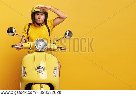 Concentrated Male Driver In Helmet On Scooter, Keeps Palm Near Forehead, Poses On Motorbike, Carries