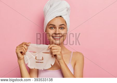 Complexion Treatment Concept. Young Pretty Woman Holds Gel Peel Mask For Face, Has Cheerful Expressi