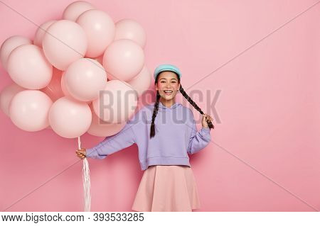 Pretty Cheerful Asian Teenage Girl Comes On Holiday With Bunch Of Airballoons, Has Two Dark Long Pla