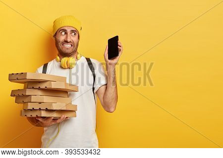 Photo Of Puzzled Delivery Man Carries Pizza Boxes, Holds Modern Smartphone With Mockup Screen, Recei