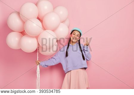 Image Of Happy Girl Greets Friends On Balloon Party, Has Two Plaits, Wears Purple Sweater And Skirt,