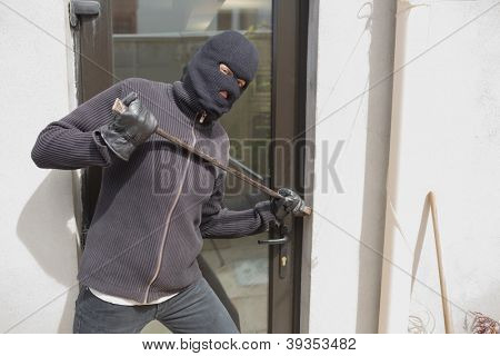 Robber breaking into house through back door using crow bar