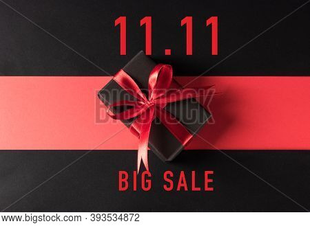 11:11 Sale Shopping And Boxing Day Concept, Gift Box Wrapped Black Paper And Red Bow Ribbon Present