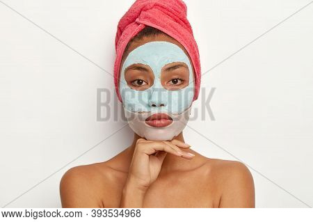Calm Young Female Model Enjoys Daily Skincare Regime, Applies Soothing Mask On Face, Reduces Surface