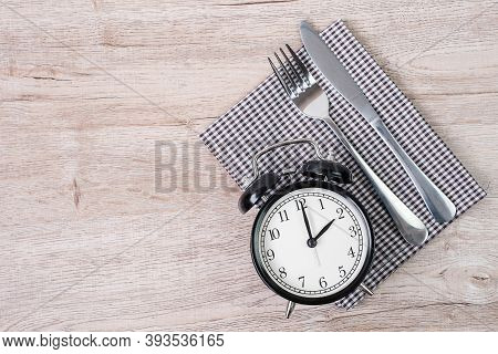 Top View Alarm Clock With Knife And Fork On Table Cloth Background. Intermittent Fasting, Ketogenic