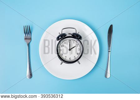 Top View Alarm Clock On White Plate With Knife And Fork On Blue Background. Intermittent Fasting, Ke