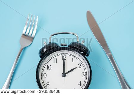 Top View Alarm Clock With Knife And Fork On Blue Background. Intermittent Fasting, Ketogenic Dieting