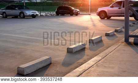 Focus At Concrete Wheel Stops On Foreground With Empty Space And  Three Cars Parked In Outdoor Parki