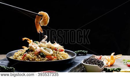 Selective Focus At Chopstick Pickup Shrimp With Stir Fry Instant Noodles Spicy Seafood In Black Plat