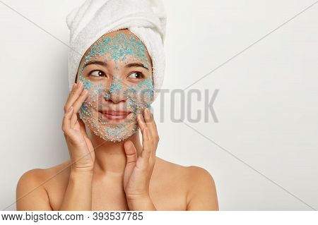 Photo Of Delighted Female Model Stands Topless Against White Background, Touches Face Skin, Makes Pe
