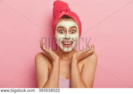 Joyous Young Lady With Cheerful Expression, Spreads Palms Near Face, Applies Natural Clay Mask For L