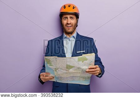 Photo Of Dissatisfied Man Builder Director Holds Map, Studies Location For New Construction, Unhappy
