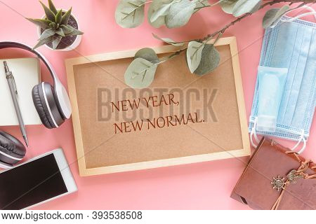 New Year New Normal On Wooden Letter Board With Stationery, Smartphone, Mask And Hand Sanitizer On P