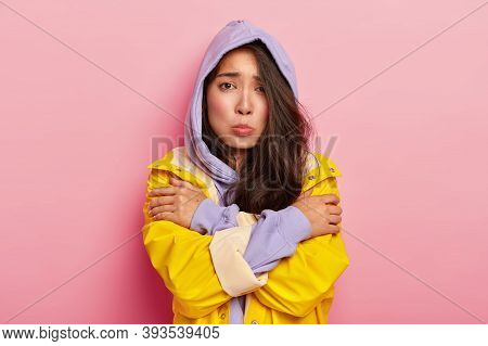 Unhappy Young Girl Feels Lonely And Cold, Looks Sadly At Camera, Keeps Hands Crossed, Wears Hoody An