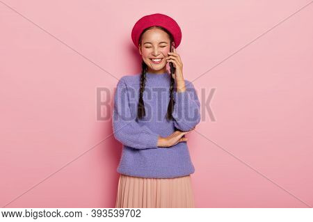 Overjoyed Pleased Woman With Asian Appearance, Enjoys Funny Telephone Conversation With Friend, Keep