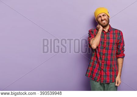 Photo Of Dissatisfied Young Man With Bristle, Feels Stiffness In Neck, Tilts Head, Clenches Teeth, D