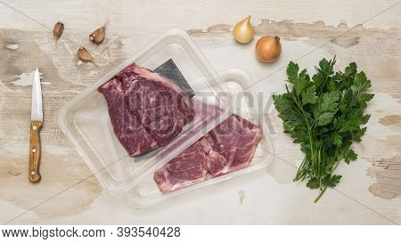 A Bunch Of Parsley And Beef Steaks In Vacuum Packaging On A Wooden Background. Sealed Packaging For