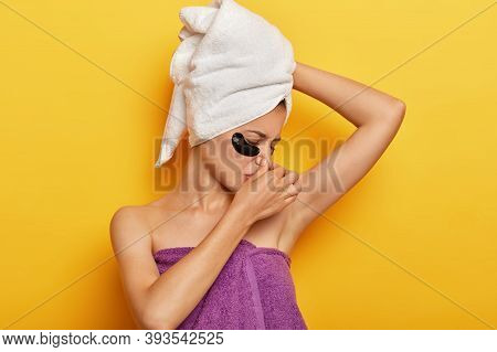 Displeased Young Lady Smells Sweaty Armpit, Covers Nose From Unpleasant Scent, Applies Undereye Patc
