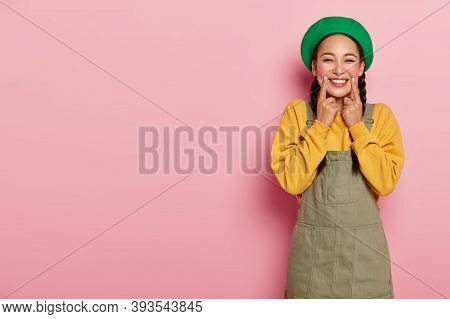 Portrait Of Pretty Joyous Girl With Rouge Cheeks, Keeps Index Fingers Near Corner Of Lips, Smiles Si