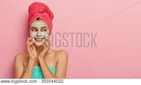 Beauty And Health Care Concept. Gentle Positive Woman Applies Facial Mask, Pampers Skin After Taking
