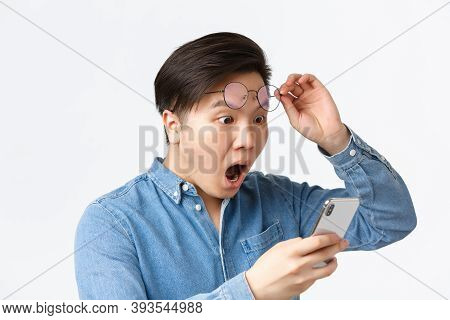Close-up Of Shocked Asian Man Take-off Glasses, Gasping In Awe While Looking At Mobile Phone Screen,