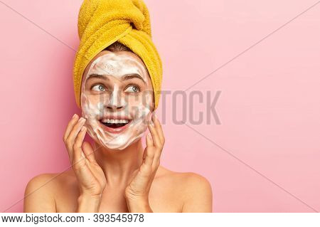 Photo Of Satisfied Pleasant Looking Woman Has Bubble Soap On Face, Pampers Complexion, Removes Dirt,