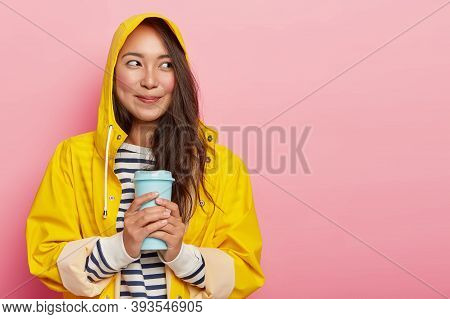 Portrait Of Cute Young Woman Wears Raincoat, Warms With Hot Beverage, Looks Happily Aside, Has Dimpl