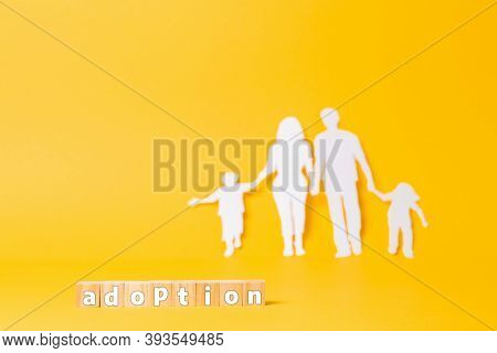 A Family Cut Out Of White Paper On A Yellow Background. Wooden Cubes With The Inscription Adoption.